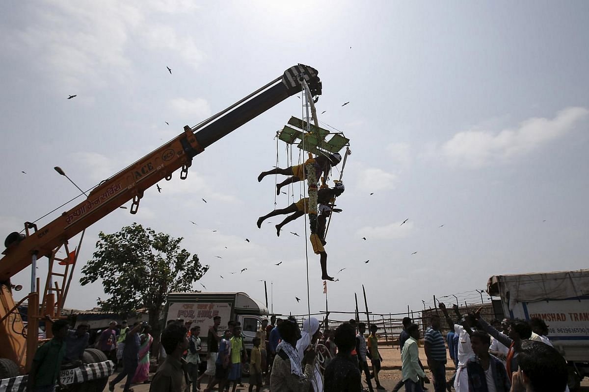 Devotees suspending themselves with pierced metal hooks from a crane during a religious procession dedicated to Goddess Mariamman in Mumbai, India, on April 21, 2016.