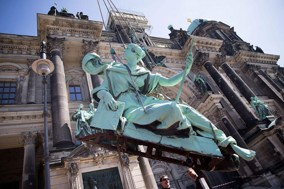 A 700kg angel is lifted by a crane from the Berlin Cathedral for restoration in Berlin, Germany, on April 21, 2016.