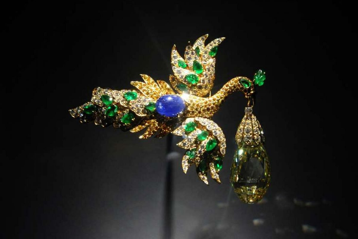 A bird clip and pendant made of yellow gold, emeralds, sapphires and a 96.62-carat yellow diamond. The wings can be detached to wear as earrings and the yellow diamond a pendant.