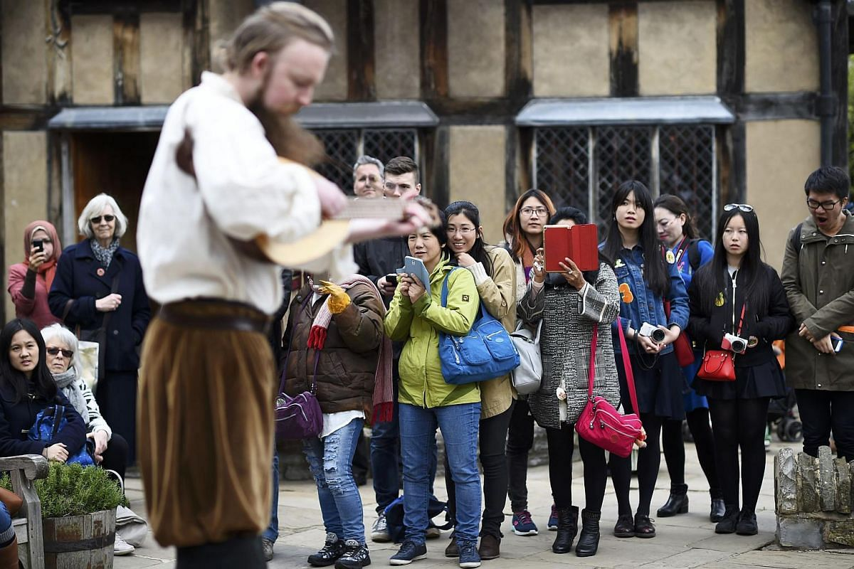 Tourists watch actors perform at the house where William Shakespeare was born during celebrations to mark the 400th anniversary of the playwright's death in Stratford-Upon-Avon, Britain, on April 23, 2016.