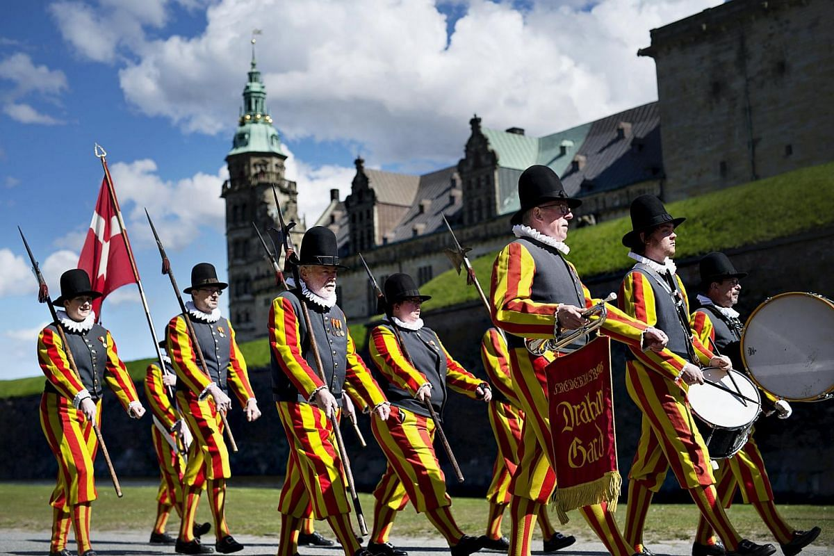 Soldiers in old-fashioned uniforms march in Elsinore with Kronborg Castle in the background to mark the 400th anniversary of the death of William Shakespeare, in Denmark, on April 23, 2016.