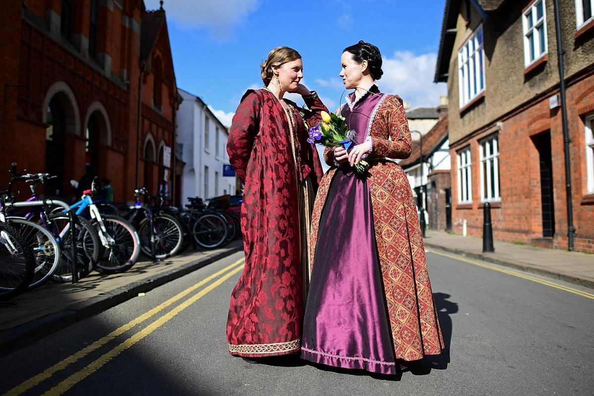 Two women in costumes talk in a side-street as they prepare for the parade marking the 400 years since the death of William Shakespeare, in Stratford-upon-Avon in central England on April 23, 2016.