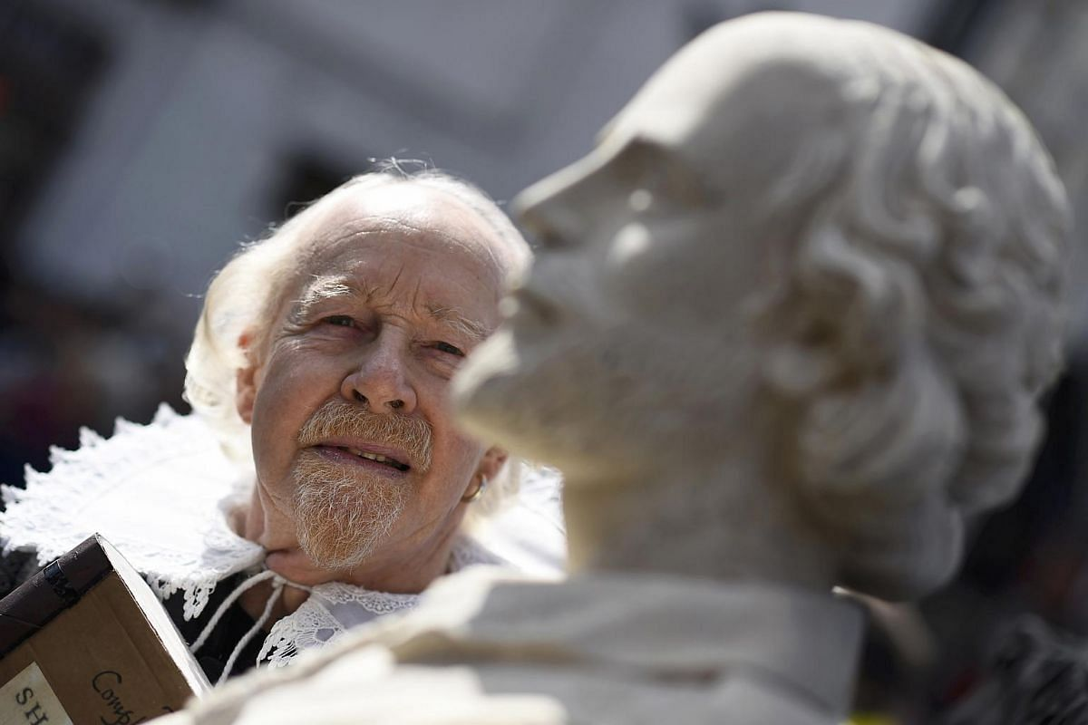 A man dressed as William Shakespeare poses next to a bust of the playwright during celebrations to mark the 400th anniversary of Shakespeare's death in the city of his birth, Stratford-Upon-Avon, Britain, on April 23, 2016.