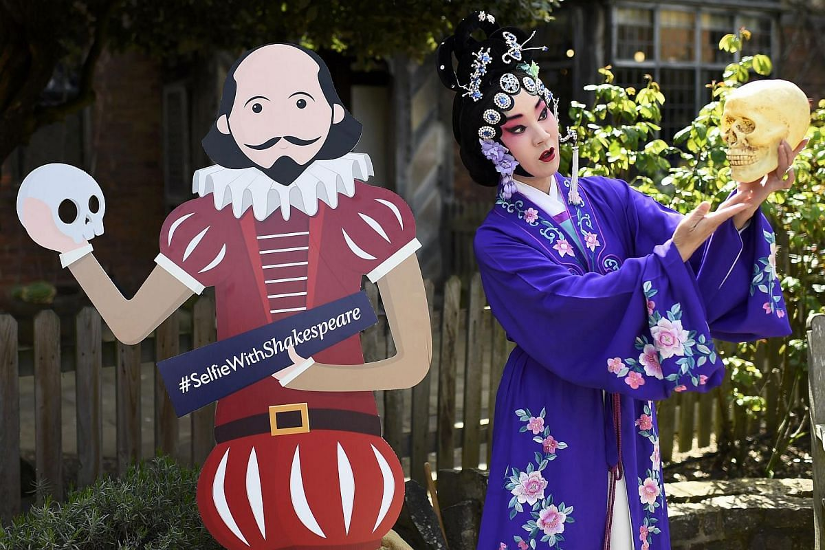 A Chinese performer poses for a friend outside the house where William Shakespeare was born during celebrations to mark the 400th anniversary of the playwright's death in Stratford-Upon-Avon, Britain, on April 23, 2016.