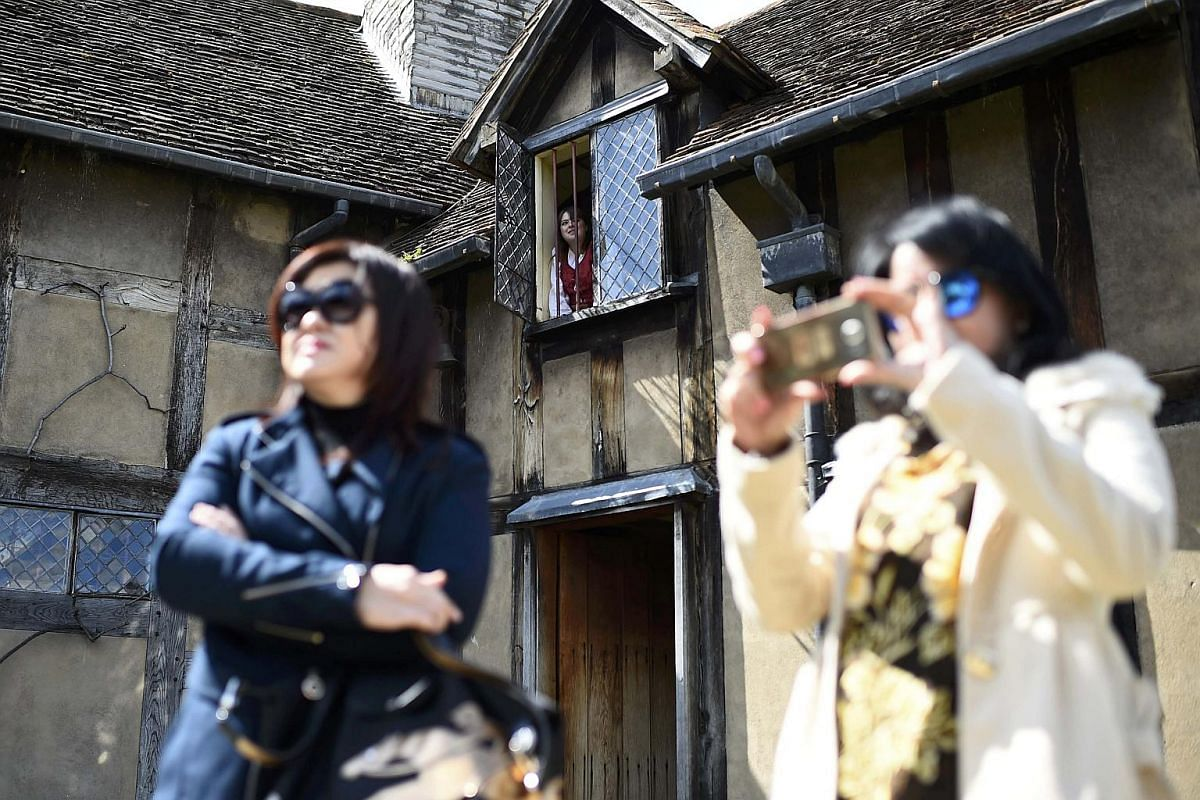 Tourists watch actors perform the Romeo and Juliet window scene at the house where William Shakespeare was born during celebrations to mark the 400th anniversary of the playwright's death in Stratford-Upon-Avon, Britain, on April 23, 2016.