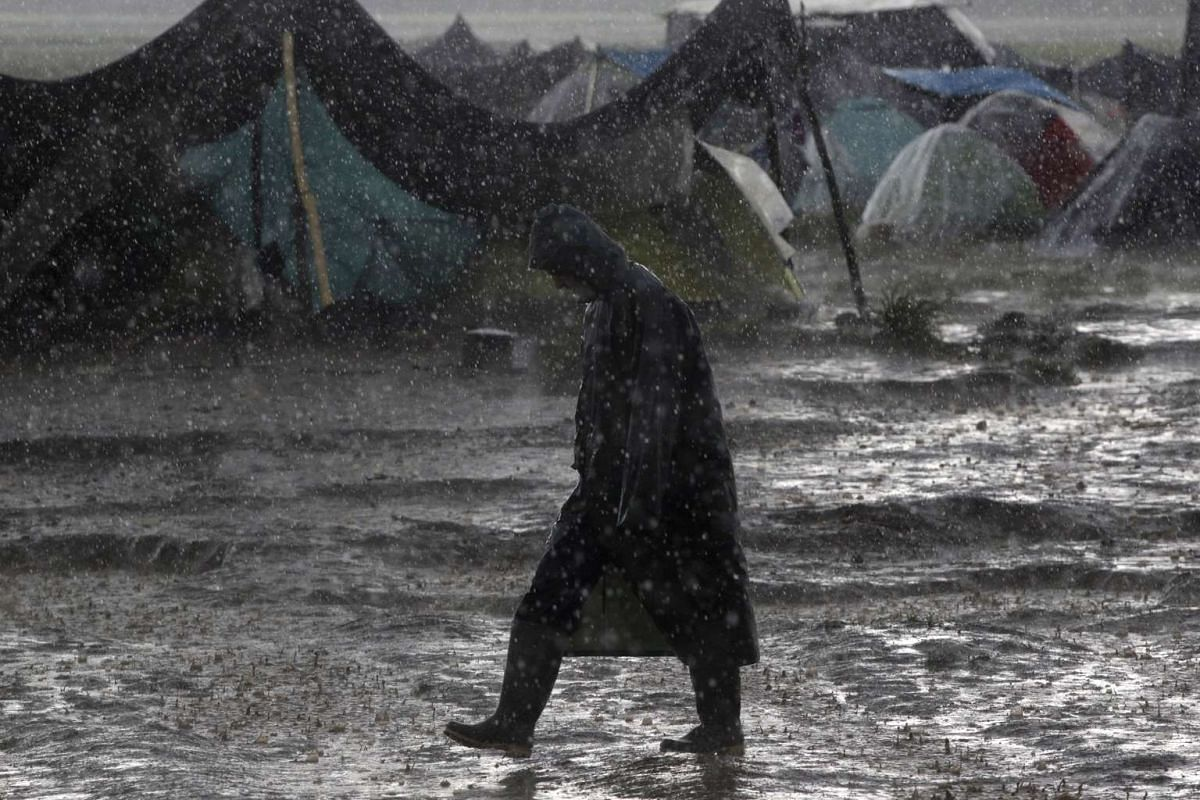 A refugee walks under heavy rainfall at a makeshift camp for migrants and refugees at the Greek-Macedonian border near the village of Idomeni.