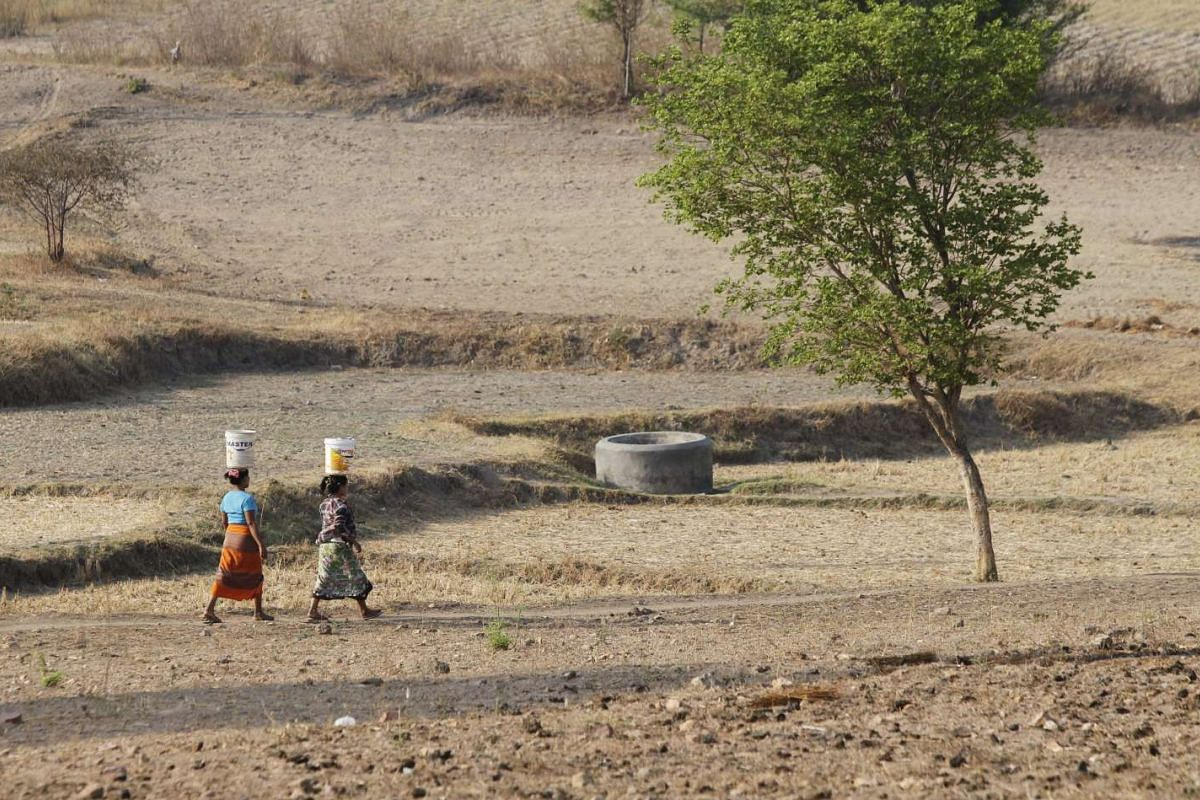 Two Myanmar women carrying buckets to collect drinking water in the outskirts of Naypyitaw, Myanmar, on April 25, 2016. Myanmar might suffer from drought and drinking water shortages in at least 10 regions, in the summer of 2016, due to the El Nino w
