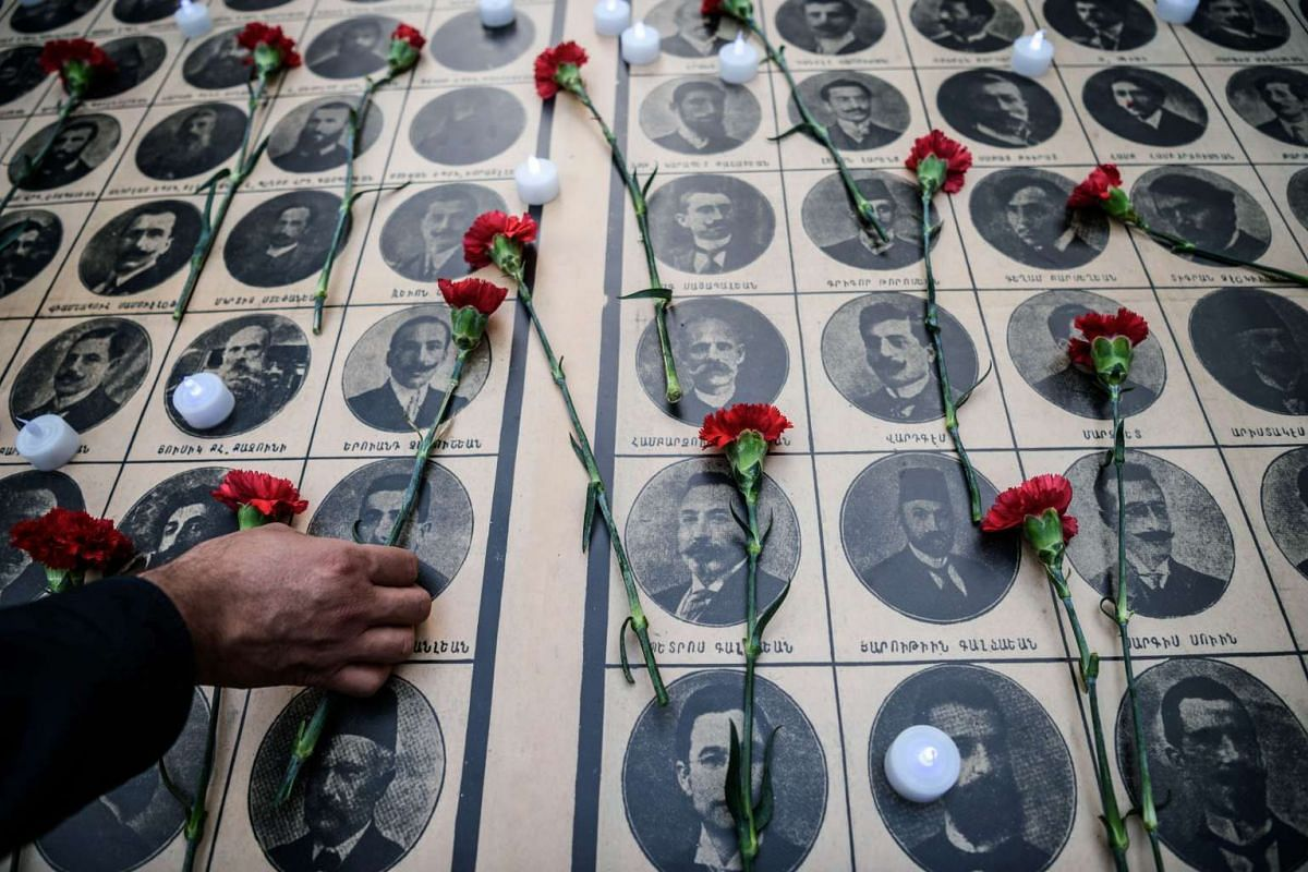 People laying red carnations on pictures of Armenian intellectuals who were detained and deported in 1915, during a rally in Istanbul commemorating the Armenian Genocide, on April 24, 2016.