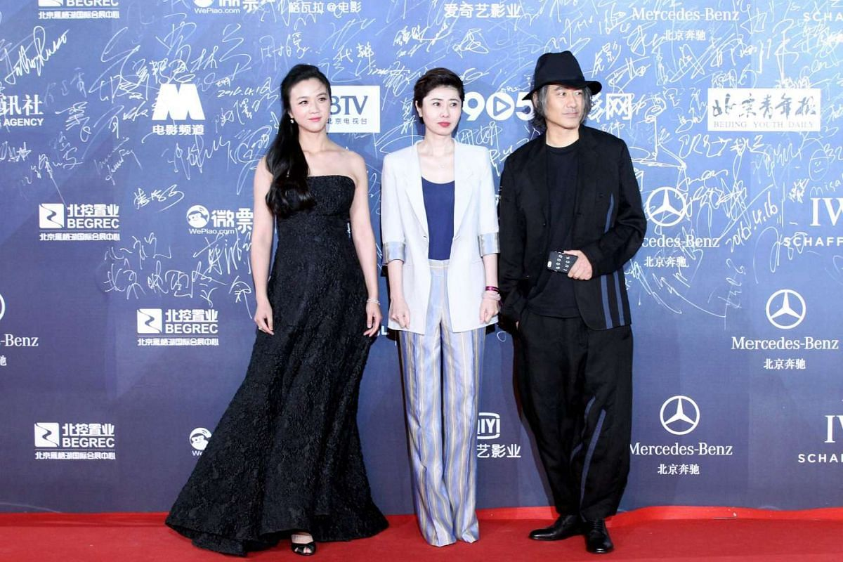 Chinese actress Tang Wei, Chinese director Xue Xiaolu and Chinese actor Wu Xiubo posing on the red carpet.