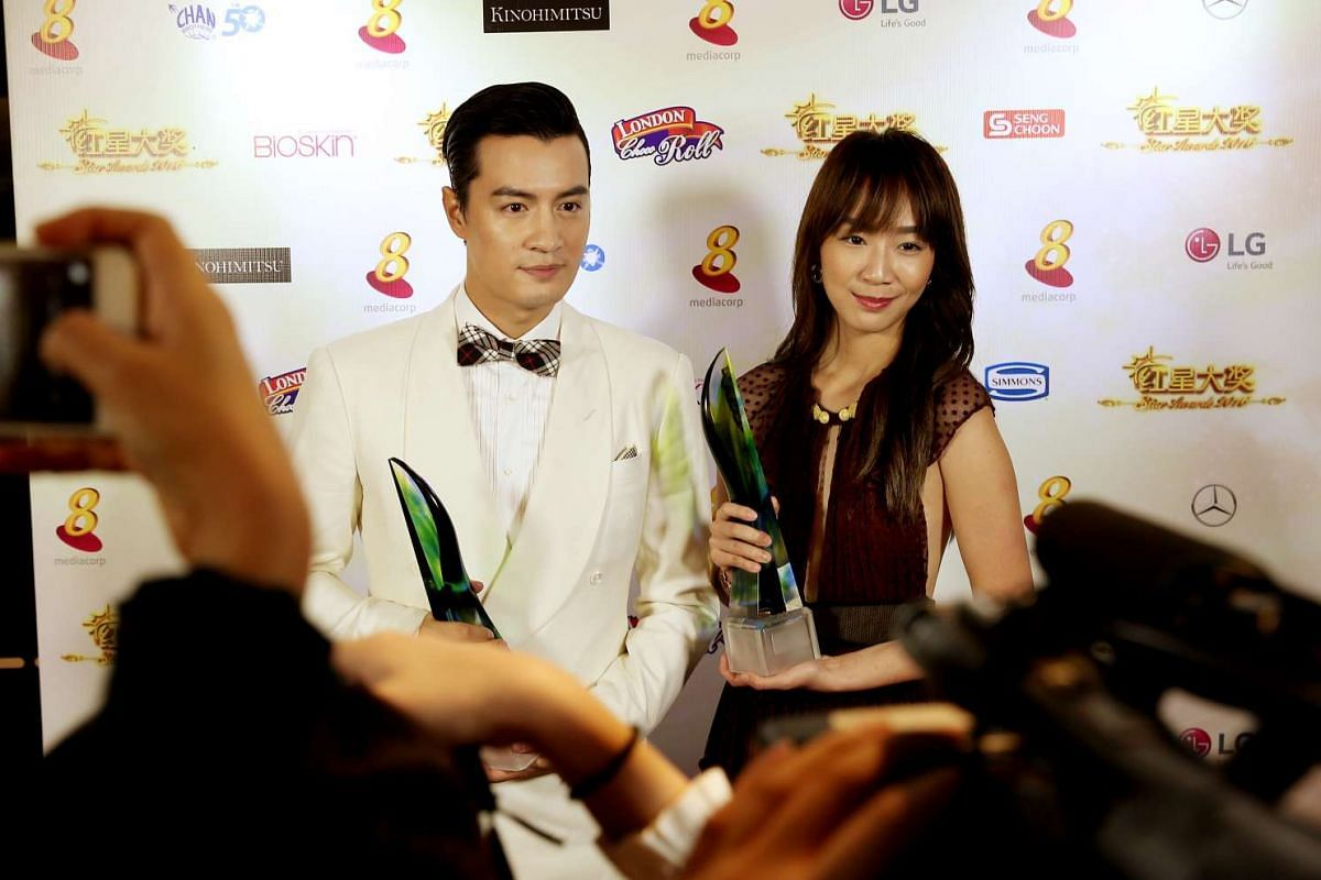 Zhang Zhenhuan and Julie Tan pose with their Best Supporting Actor and Actress awards at the Star Awards 2016.