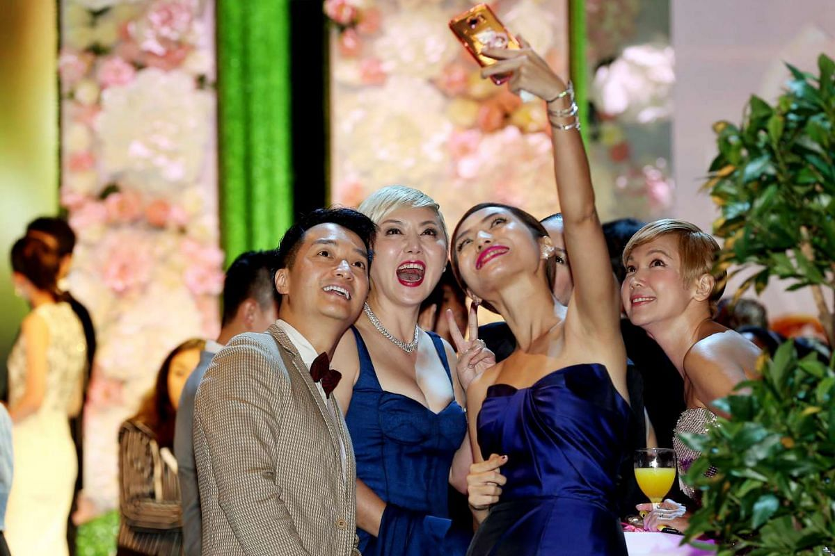 Quan Yi Fong (second from left), Vivian Lai (second from right) and Kim Ng (right) take a wefie during the Star Awards 2016.