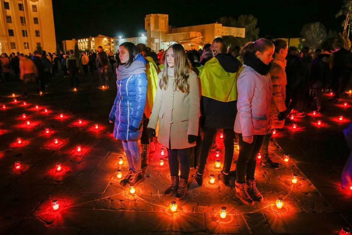 Ukrainians light candles near the memorial for 'liquidators' who died during cleaning up works after the Chernobyl nuclear power plant disaster, during a ceremony in Slavutich city on April 26, 2016.
