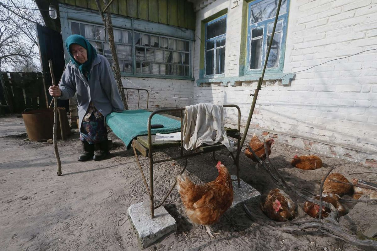 Maria Semenyuk, a resident of the Chernobyl zone sits near her house in the deserted village of Paryshev on April 11, 2016.