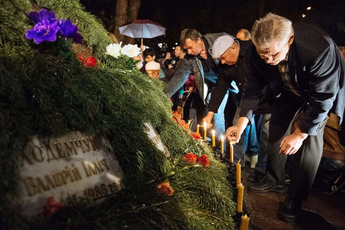 People light candles during a ceremony for liquidators who died during cleaning up works after the Chernobyl nuclear power plant disaster, in Kiev, Ukraine, on April 26, 2016.