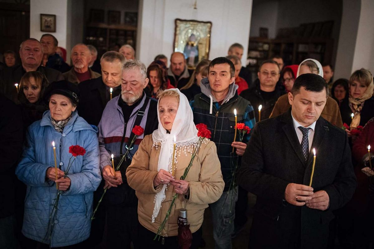 Ukrainians hold flowers and candles in a church as they attend a ceremony for liquidators who died during cleaning-up works after the Chernobyl nuclear power plant disaster, in Kiev, Ukraine, on April 26, 2016.