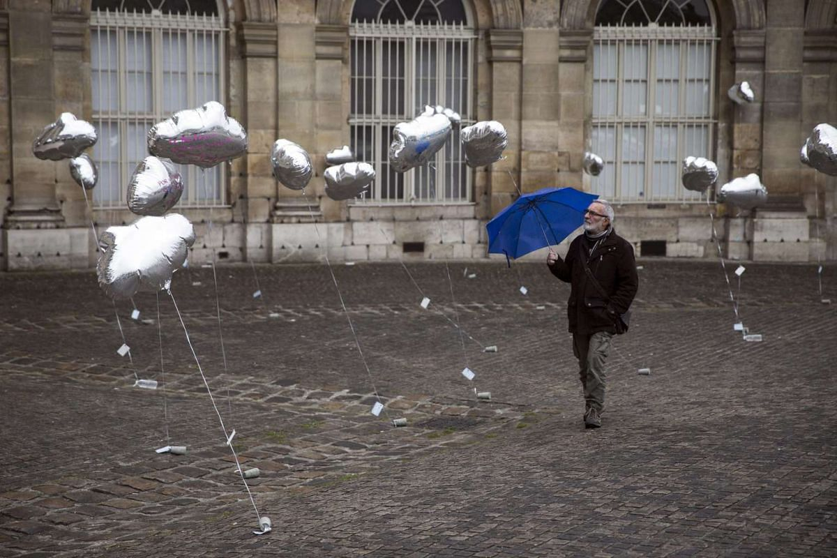A man with an umbrella watches cloud-shaped balloons during a demonstration against the use of nuclear power plants in Paris, France, on April 25, 2016.