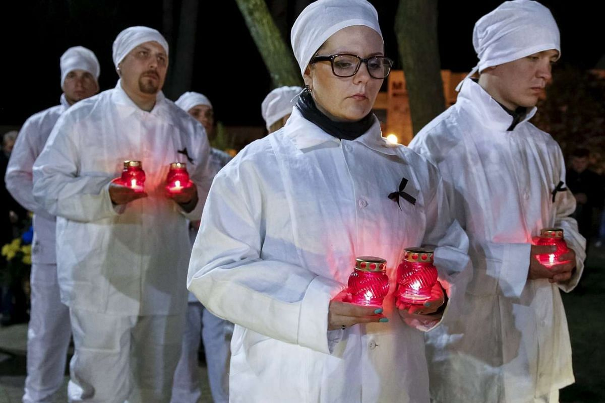 Staff of the Chernobyl nuclear plant hold candles at a memorial dedicated to firefighters and workers who died after the Chernobyl nuclear disaster, in Slavutych, Ukraine, on April 26, 2016.