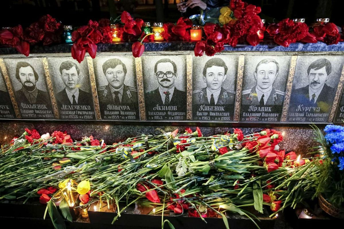 Flowers are laid in front of a memorial, dedicated to firefighters and workers who died after the Chernobyl nuclear disaster, during a night service in Slavutych, Ukraine, on April 26, 2016.