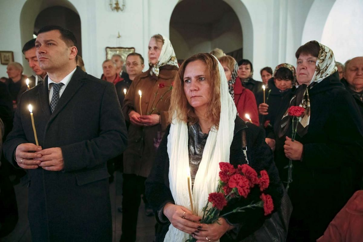 People hold flowers and candles for victims of the Chernobyl nuclear disaster during a memorial service in a church in Kiev, Ukraine, on April 25, 2016.
