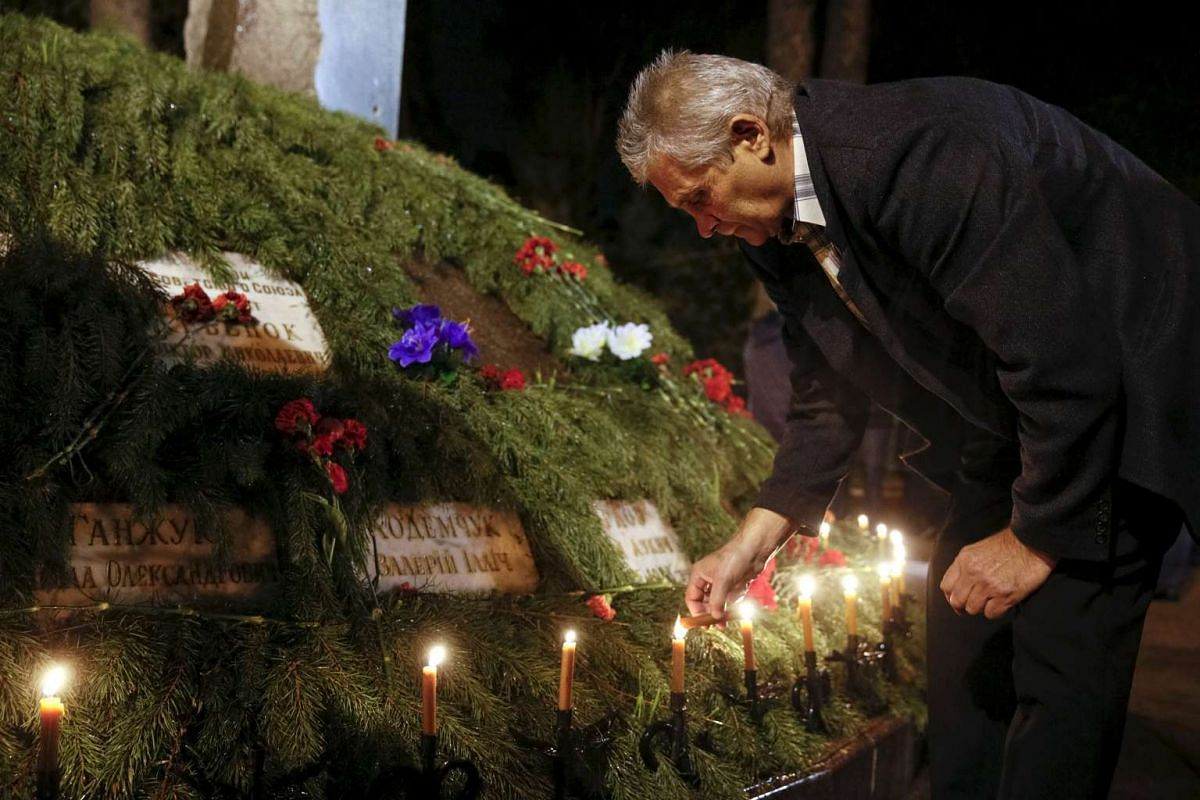 A man lights a candle after a memorial service for victims of the Chernobyl nuclear disaster in Kiev, Ukraine, on April 25, 2016.