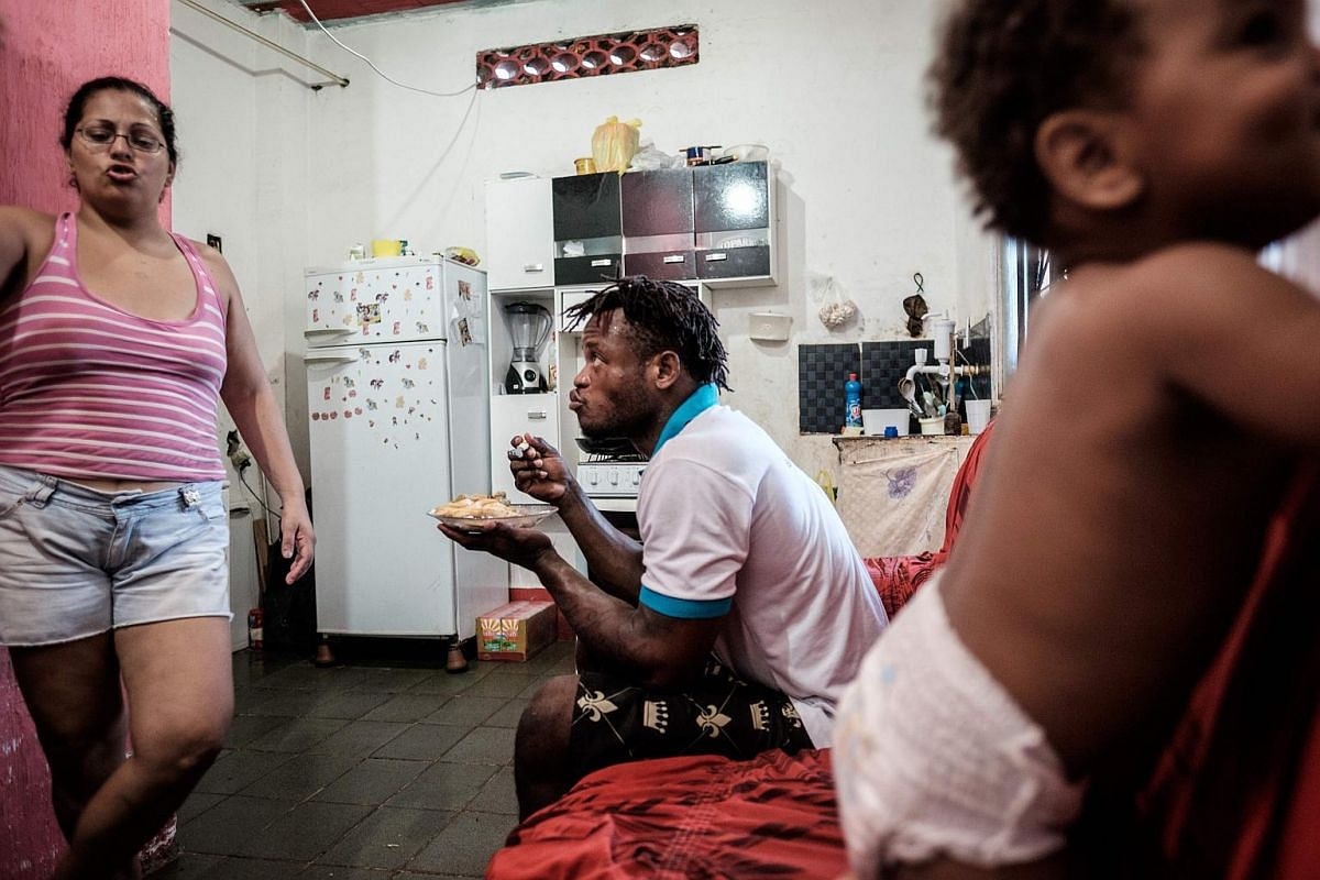 Popole Misenga (centre) having lunch with his one-year-old son Heliasin and his partner Fabiana at home in Rio de Janeiro, Brazil, on April 14, 2016.