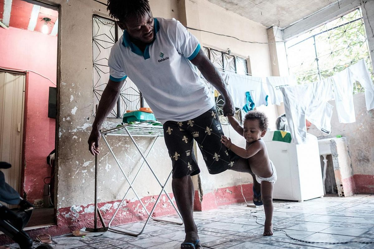 Popole Misenga (left) playing judo with his one-year-old son Heliasin at home.