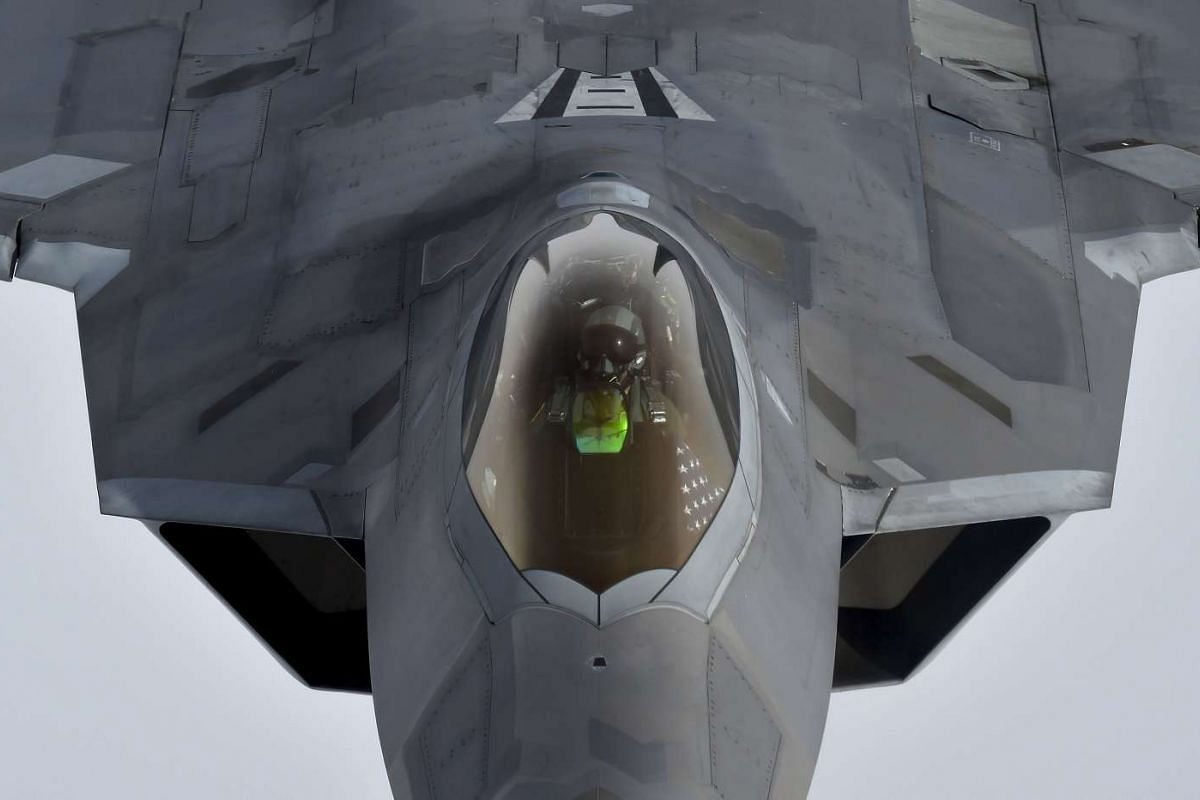 A pilot looks up from a US F-22 Raptor fighter as it prepares to refuel mid-air with refuelling plane during a flight to Britain from Romania, on April 25, 2016.