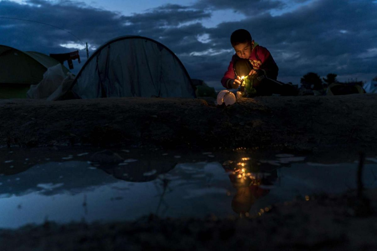 A boy burns a disposable plastic plate at a makeshift camp for migrants and refugees near the Greek-Macedonian border, on April 25, 2016.
