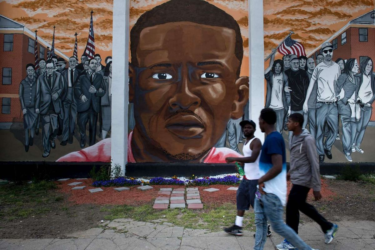 People pass a mural depicting Freddie Gray in Baltimore, Maryland, on April 25, 2016, a year after the protests that were sparked by Gray's death in police custody.