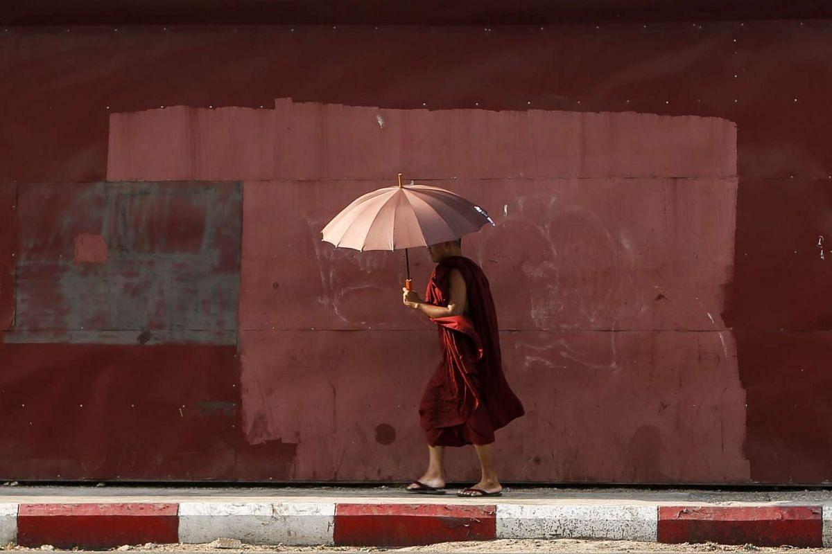 A Buddhist monk uses an umbrella to protect himself from the sun on a hot summer's day in Yangon, Myanmar on April 26, 2016.