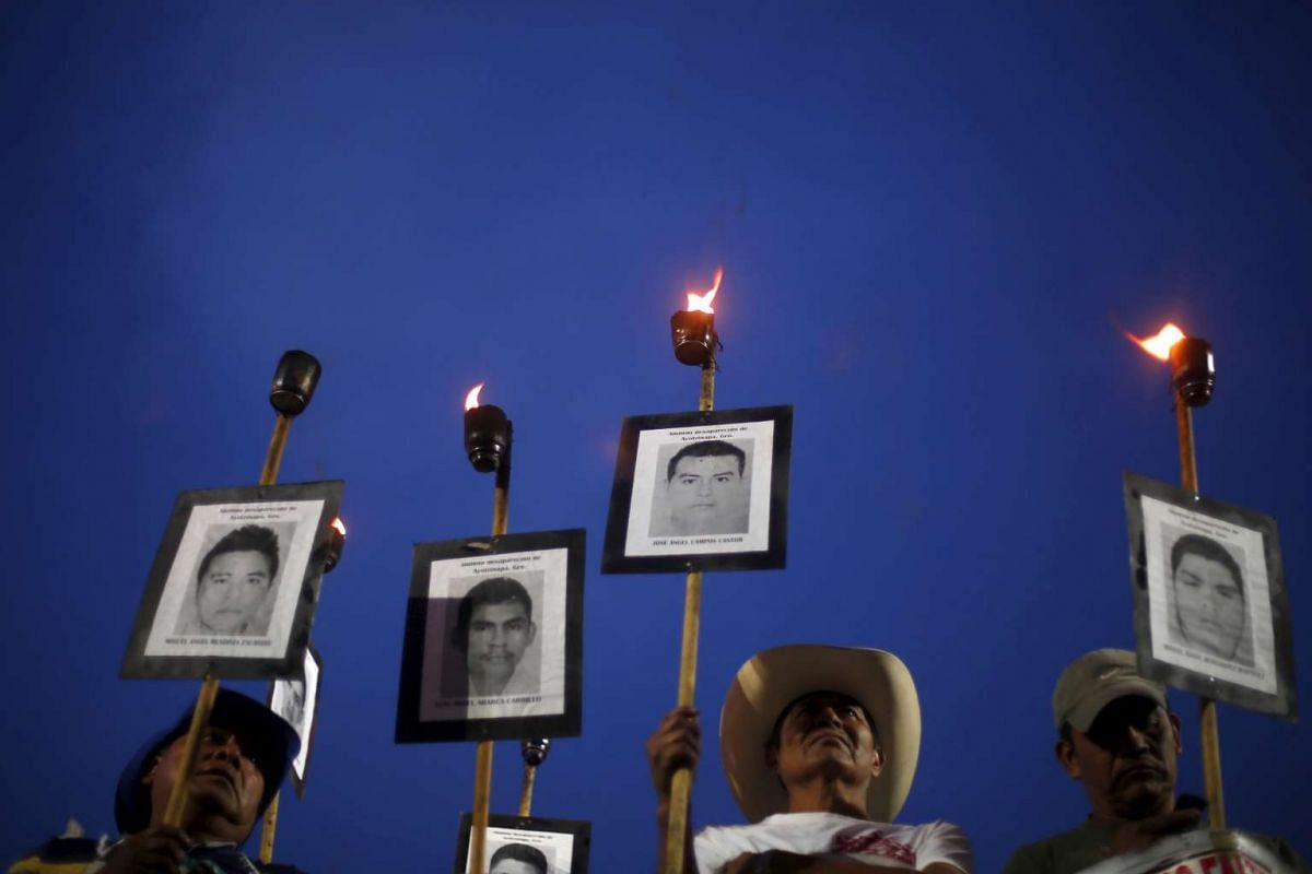 Relatives of the 43 missing students from the Teacher's Training College Ayotzinapa Raul Isidro Burgos hold torches in protest on April 26, 2016.