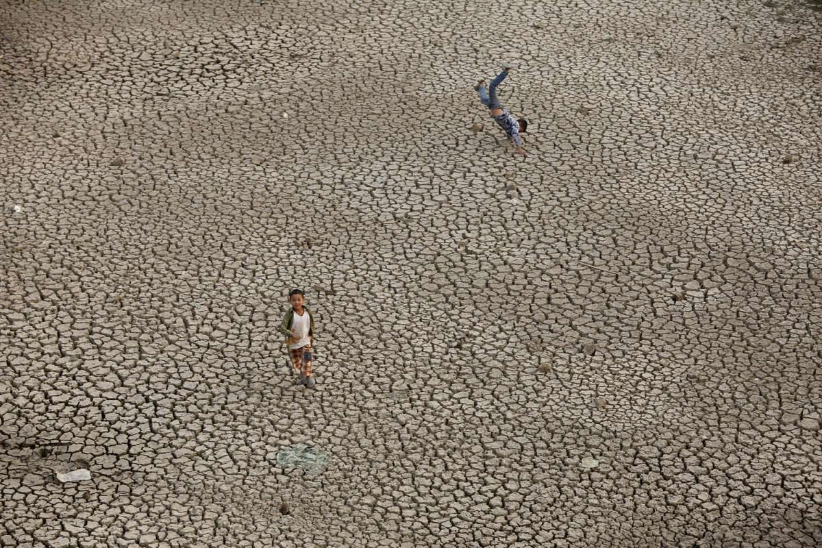 Nepalese children play at dried pang Gaun pond in Chapagau village in Lalitpur, Nepal on April 26, 2016.