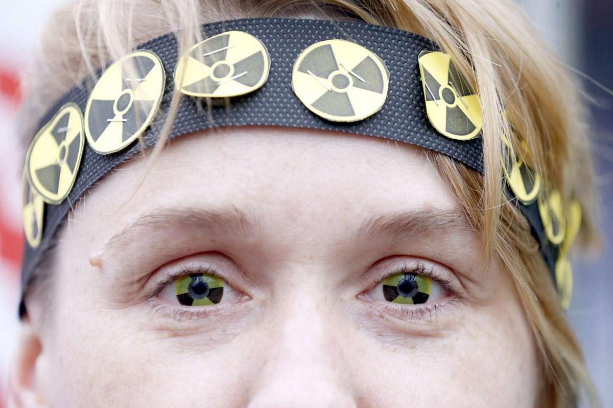 A protester wears eye-lenses with radioactive signs, as she participates in a rally to mark the 30th anniversary of the Chernobyl nuclear disaster in Minsk, Belarus, on April 26, 2016.