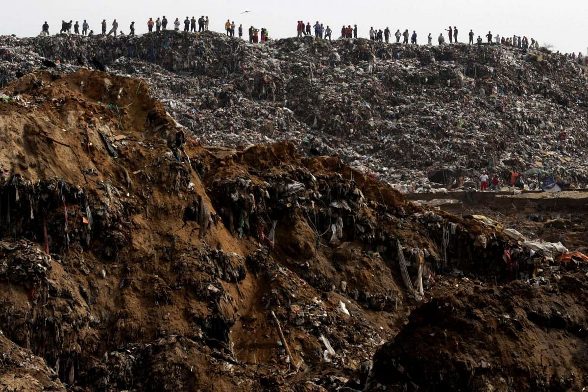 Garbage collectors lookomg at rescue teams (not pictured) working at the site where a massive pile of garbage collapsed at a landfill in Guatemala City, Guatemala, on April 27, 2016.