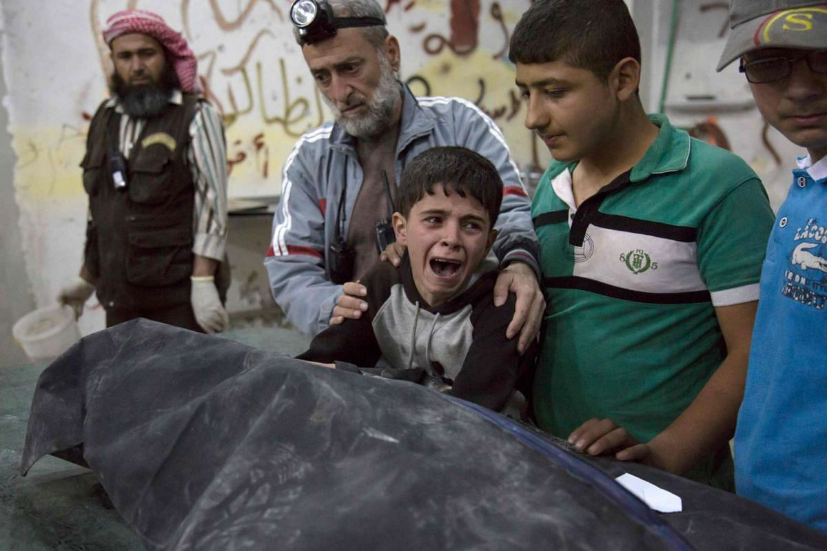A Syrian boy is comforted as he cries next to the body of a relative who died in an air strike on Wednesday, April 27, 2016, in the rebel-held neighbourhood of al-Soukour in Aleppo.