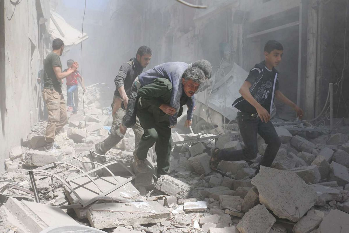 Syrians evacuating an injured man amid the rubble of destroyed buildings after an air strike on the rebel-held neighbourhood of Al-Qatarji in Aleppo on Friday, April 29, 2016.