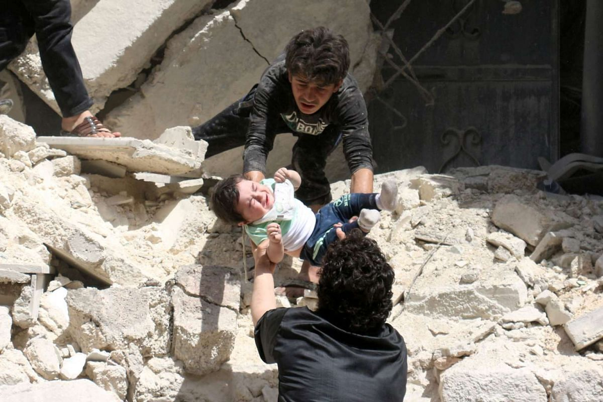 Syrians evacuating a toddler from a destroyed building after an air strike on the al-Kalasa neighbourhood in Aleppo on Thursday, April 28, 2016.