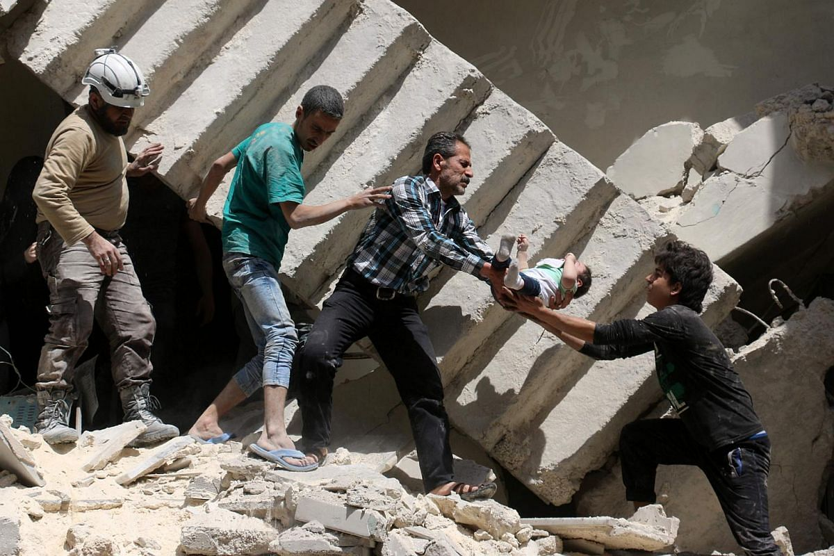 Syrian civil defence volunteers and rescuers remove a baby from under the rubble following an air strike on al-Kalasa in Syria, on April 28, 2016.