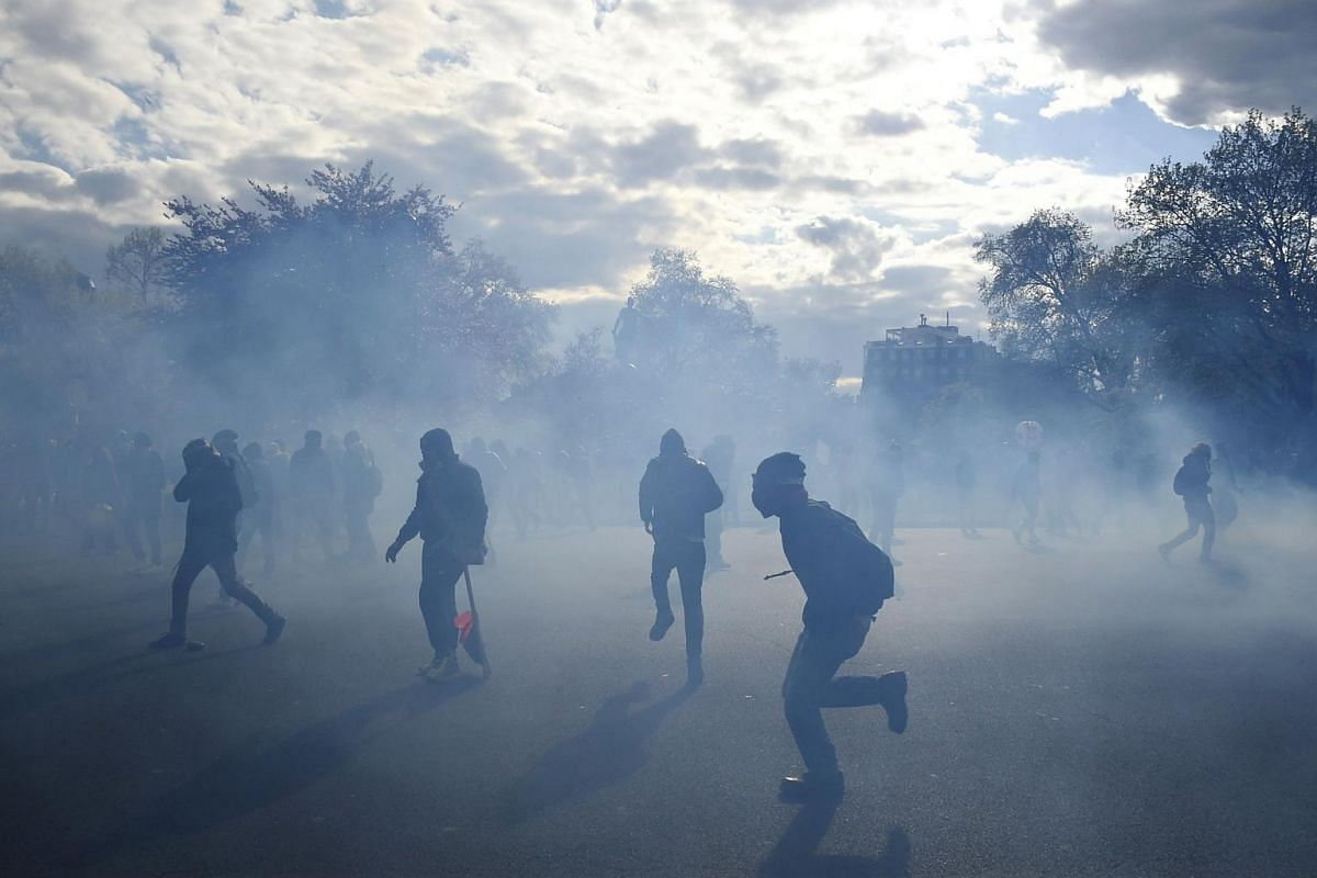 People clash with French anti-riot police during a protest against the French government's proposed labour reforms, at the Place de la Nation in Paris, on April 28, 2016.