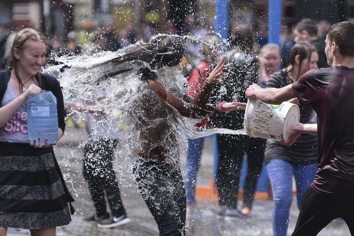 Ukrainians pour water on each other on a street in Lviv, Ukraine, May 2, 2016. The tradition of pouring water is an ancient spring ritual of cleansing on the first Monday after Orthodox Easter. PHOTO: EPA