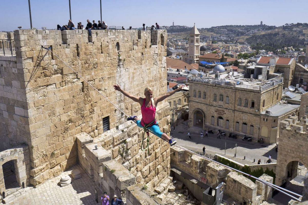 Heather Larsen from Golden, Colorado, USA performs a split while walking the slackfline or highline across two towers in the Tower of David citadel complex overlooking the Old City of Jerusalem  May 2, 2016. PHOTO: EPA