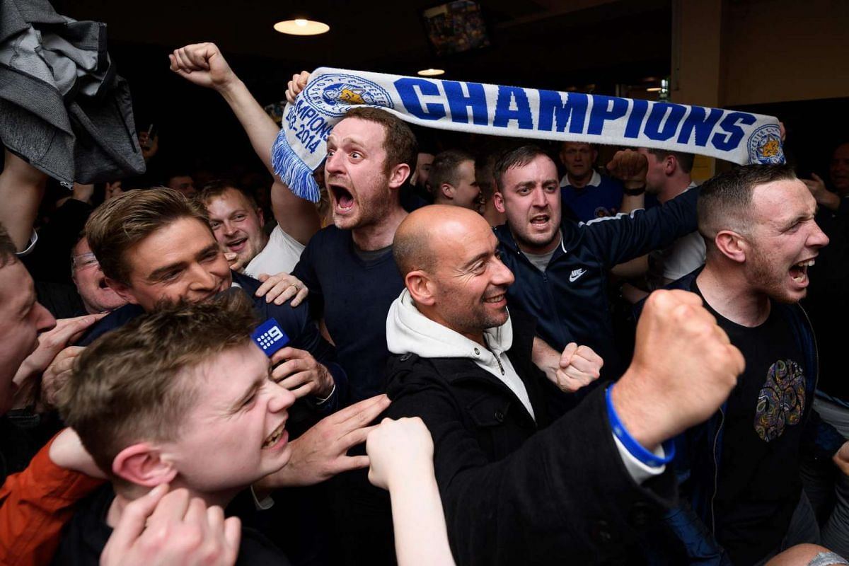 Leicester City fans celebrate winning the Premier League at the final whistle of the English Premier League football match between Chelsea and Tottenham Hotspur in a pub in central Leicester.