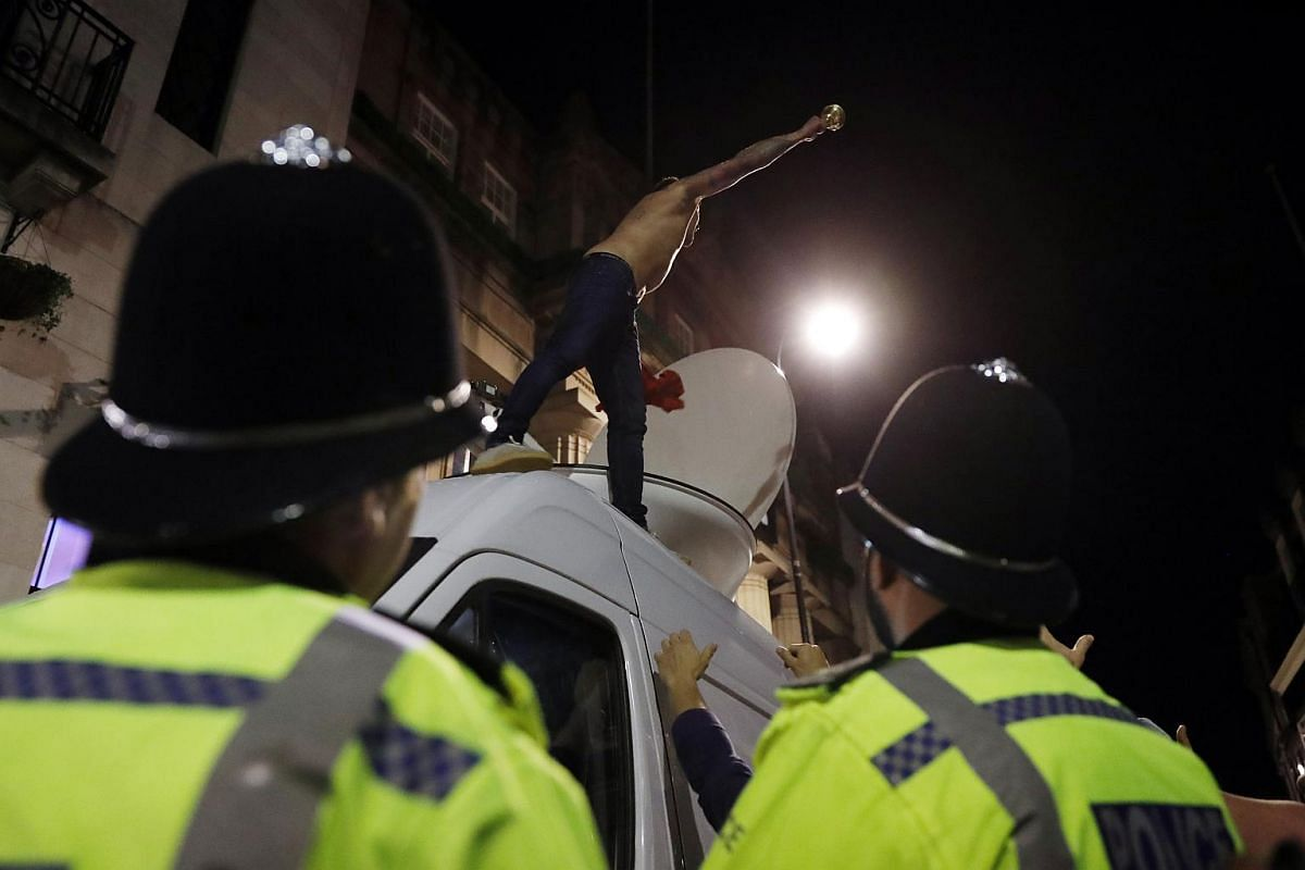 A Leicester City fan celebrates winning the Premier League on a van as Police officers look on. PHOTO: REUTERS