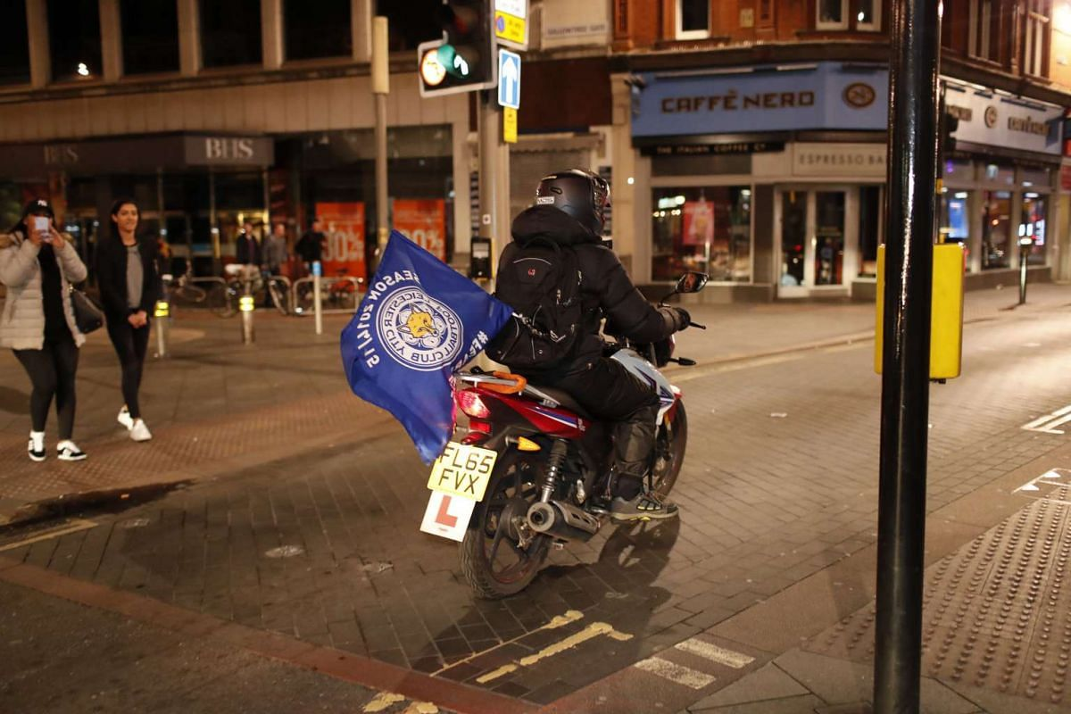 A Leicester City fan celebrates winning the Premier League with a flag on his motorcycle.
