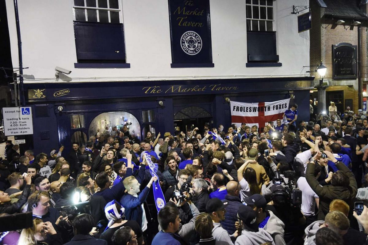 Leicester City fans celebrate winning the English Premier League after the match between Chelsea and Tottenham Hotspur, in Leicester.