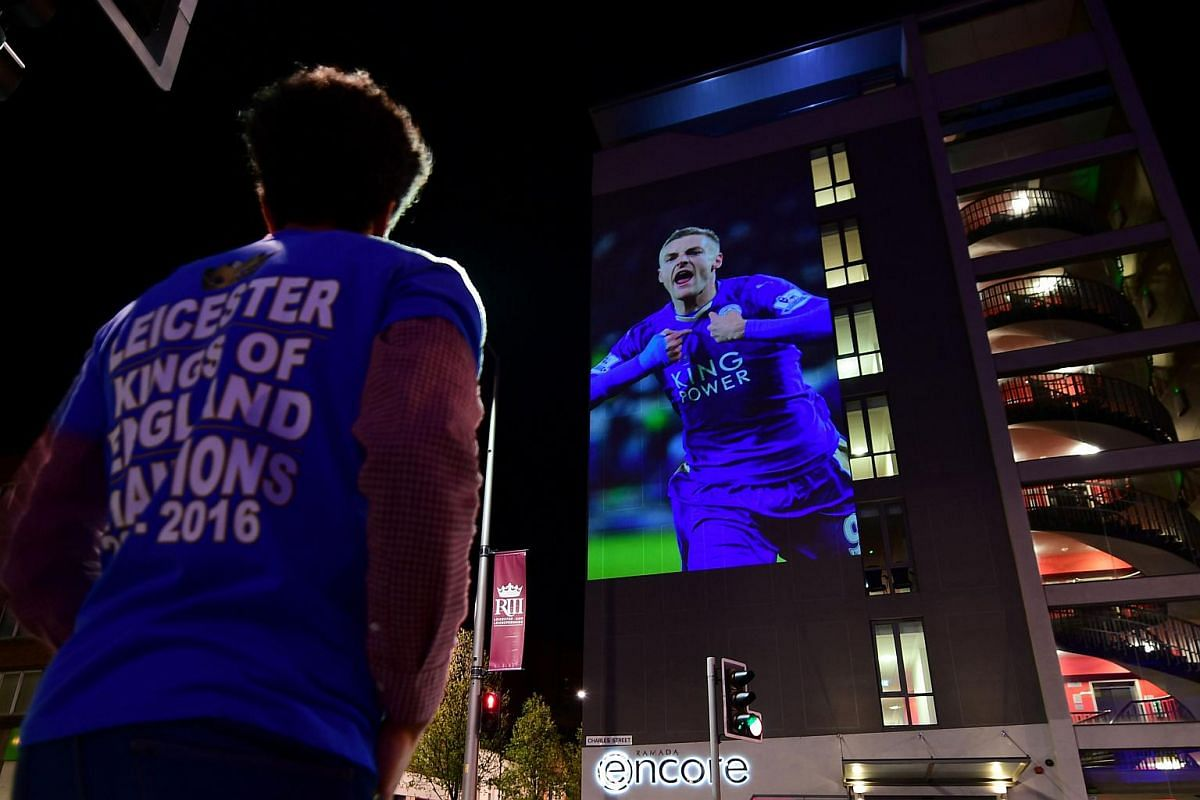 A Leicester City fan looks up at a large projection of an image of Leicester City's striker Jamie Vardy in Leicester, Britain, on May 2, 2016.
