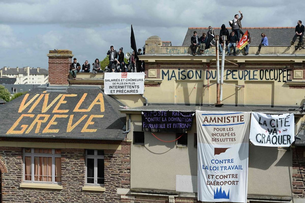 Protesters stand on the roof of the People's house on May 3, 2016 in Rennes, western France, during a protest against the government's planned labour law reforms. PHOTO: AFP