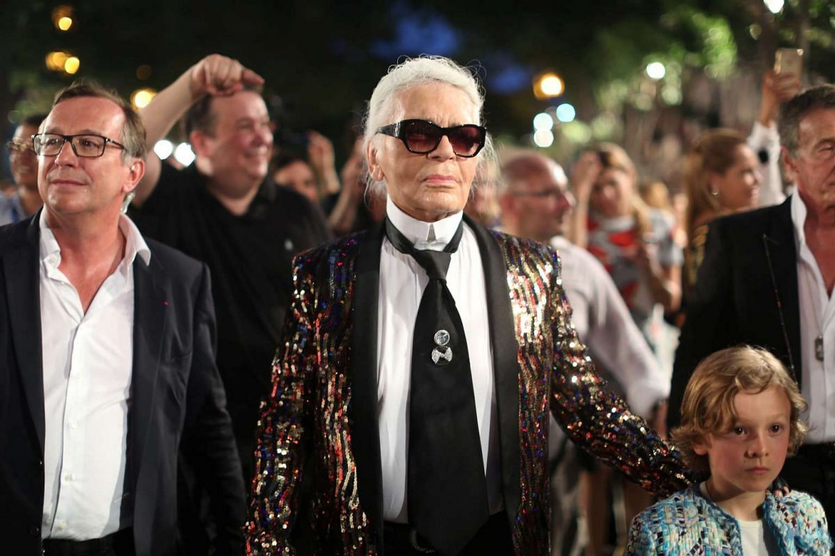 Chanel's head designer and creative director Karl Lagerfeld walks with a model after a fashion show in Cuba on May 3, 2016.