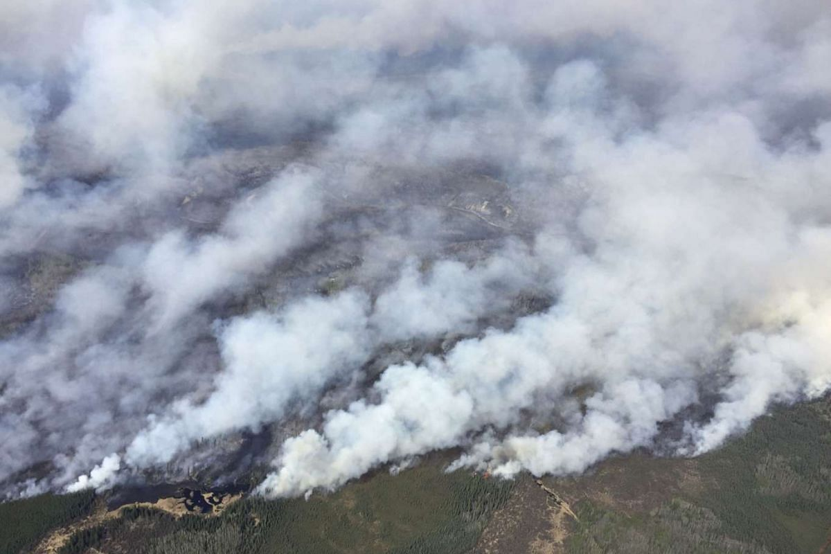 An aerial view from the helicopter of Alberta Premier Rachel Notley shows smoke rising from raging wildfires in Alberta, Canada, on May 4, 2016.