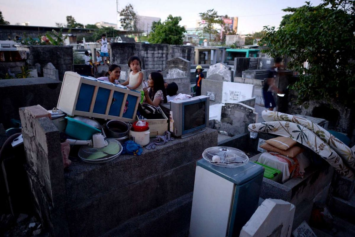 Residents stay on tombs after their makeshift houses were hit by fire inside a public cemetery in Manila, on May 4, 2016.